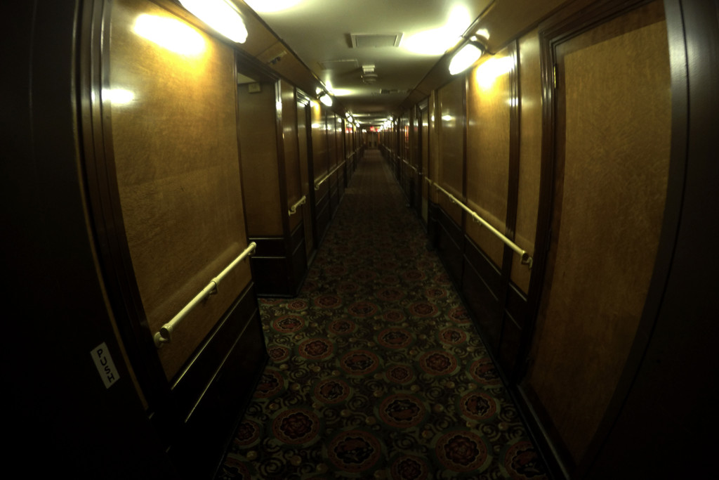 Looking down the hallways of hotel rooms inside the Queen Mary.