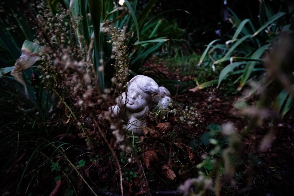 Overgrown figure in cemetery.