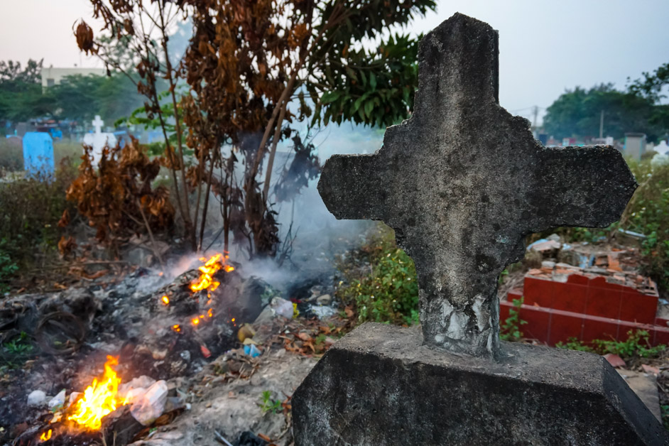 Small fires burning in the Binh Hung Hoa Cemetery of Vietnam.