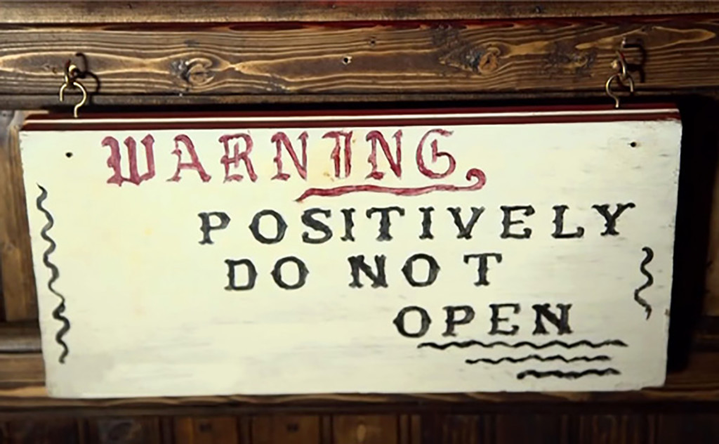Warren's Occult Museum warning sign on Annabelle doll case.