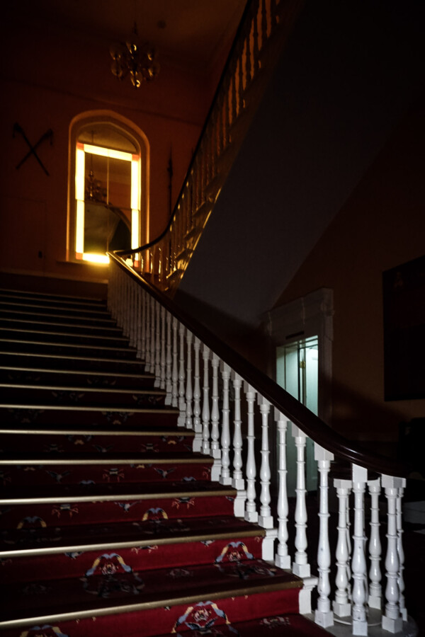 Ghost of little girl on staircase of mansion.